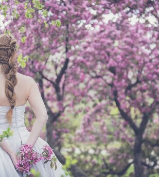 Bride standing among flowering trees.