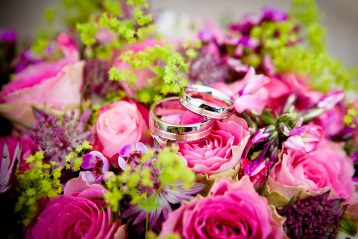 Wedding flowers with wedding rings in the center.