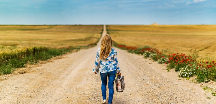 Woman walking down a long road with a suitcase.