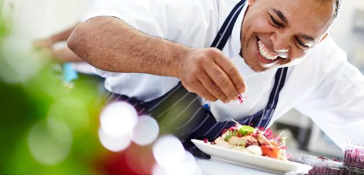 Chef finishing a plate of food.
