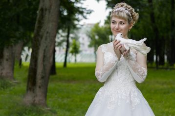 Smiling bride holding a dove.