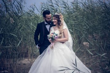 Bride and groom standing in a field.