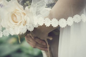 A bride standing with white roses.