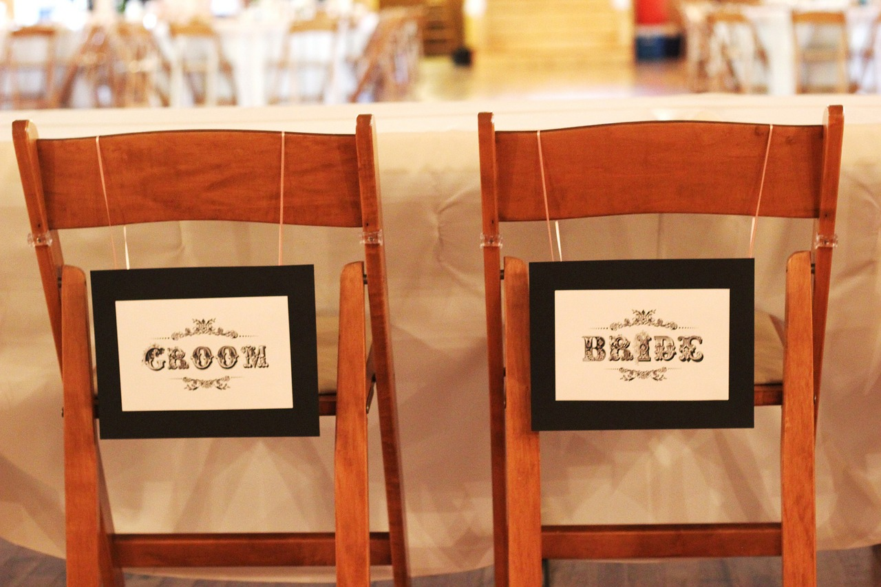Chairs with Bride and Groom signs on them.
