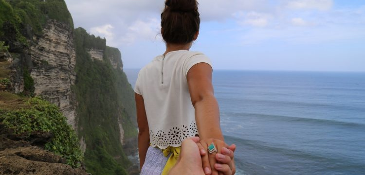 Woman holding a man's hand while standing at the edge of a cliff.