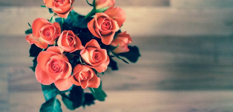 Peach colored rose bouquet in a vase.