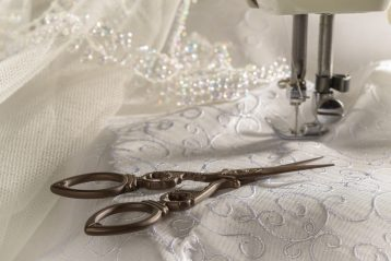 A sewing machine with a bridal gown.