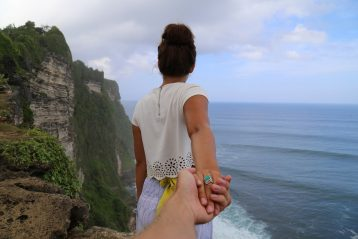 Woman on a cliff holding a man's hand.