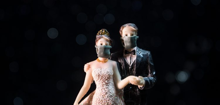 Wedding cake topper with bride and groom wearing masks.