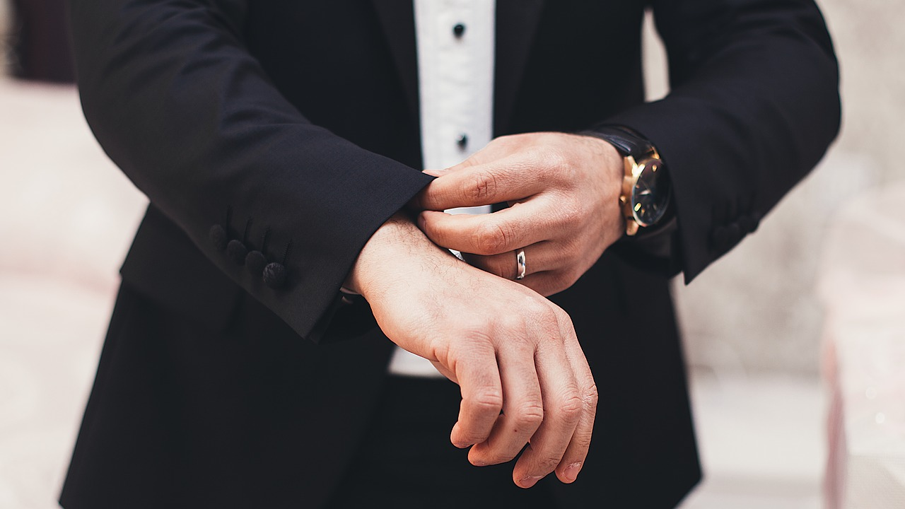 Groom wearing wedding band.