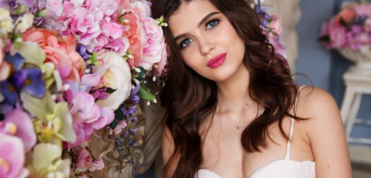 Model leaning against a row of wedding flowers.