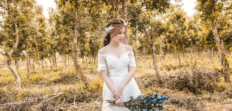 Bride standing in a forest.