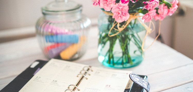 An appointment book on a table with flowers.