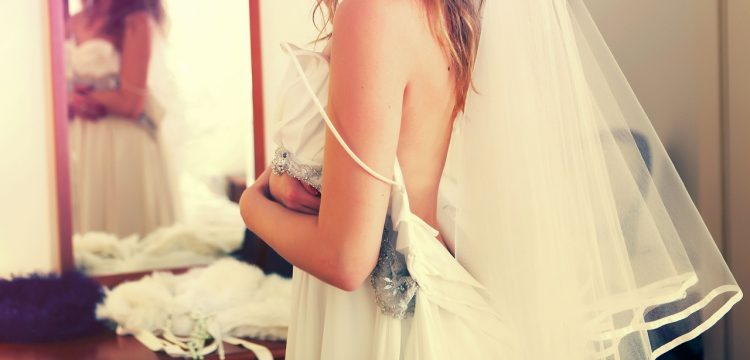 Bride trying on gown.