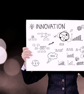 """A man holding a sign that reads, """"Innovation""""."""