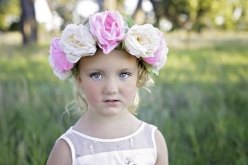A little girl with big flowers in her hair.