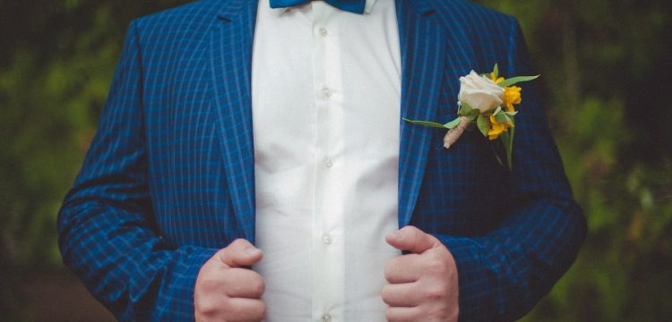 Groom in a blue suit and bow tie.