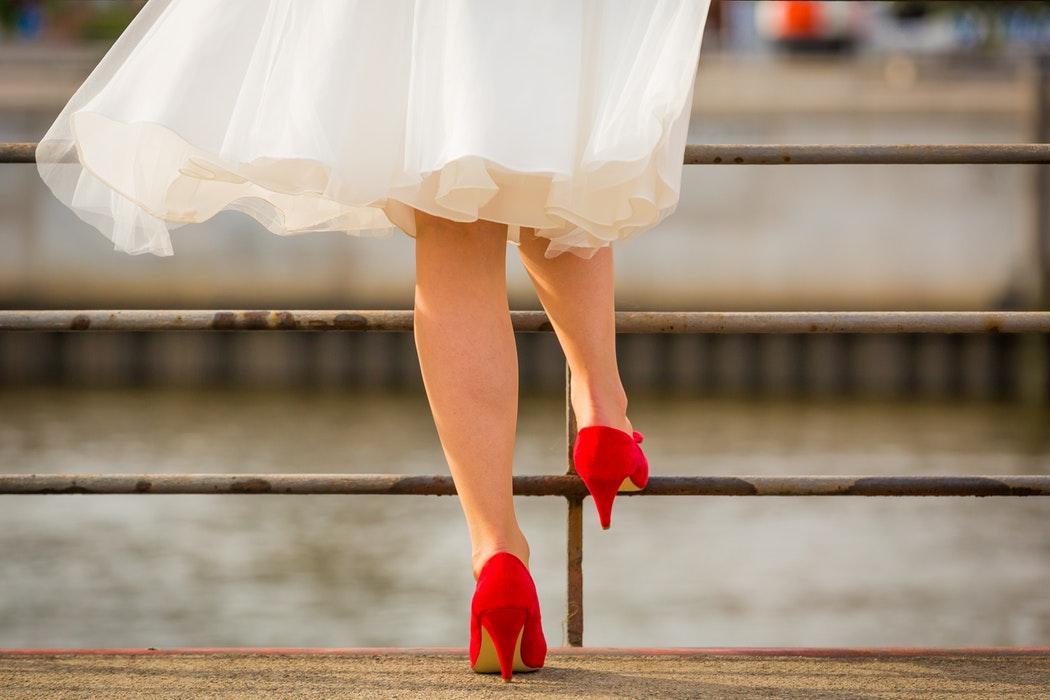 Bride in tea length dress with red heels.