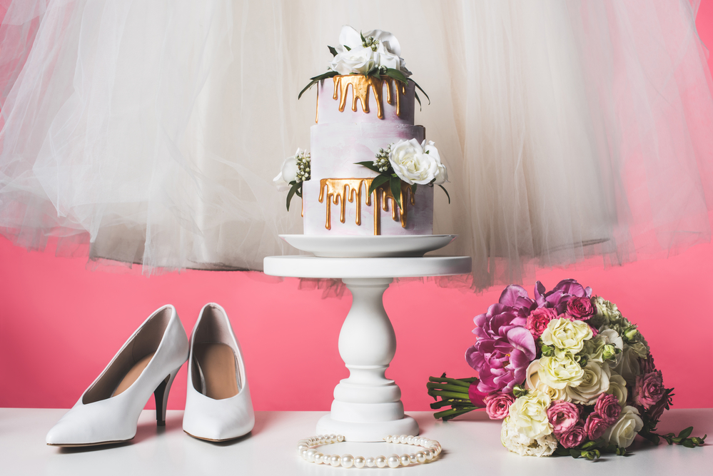 Wedding shoes, a cake, and a bouquet.