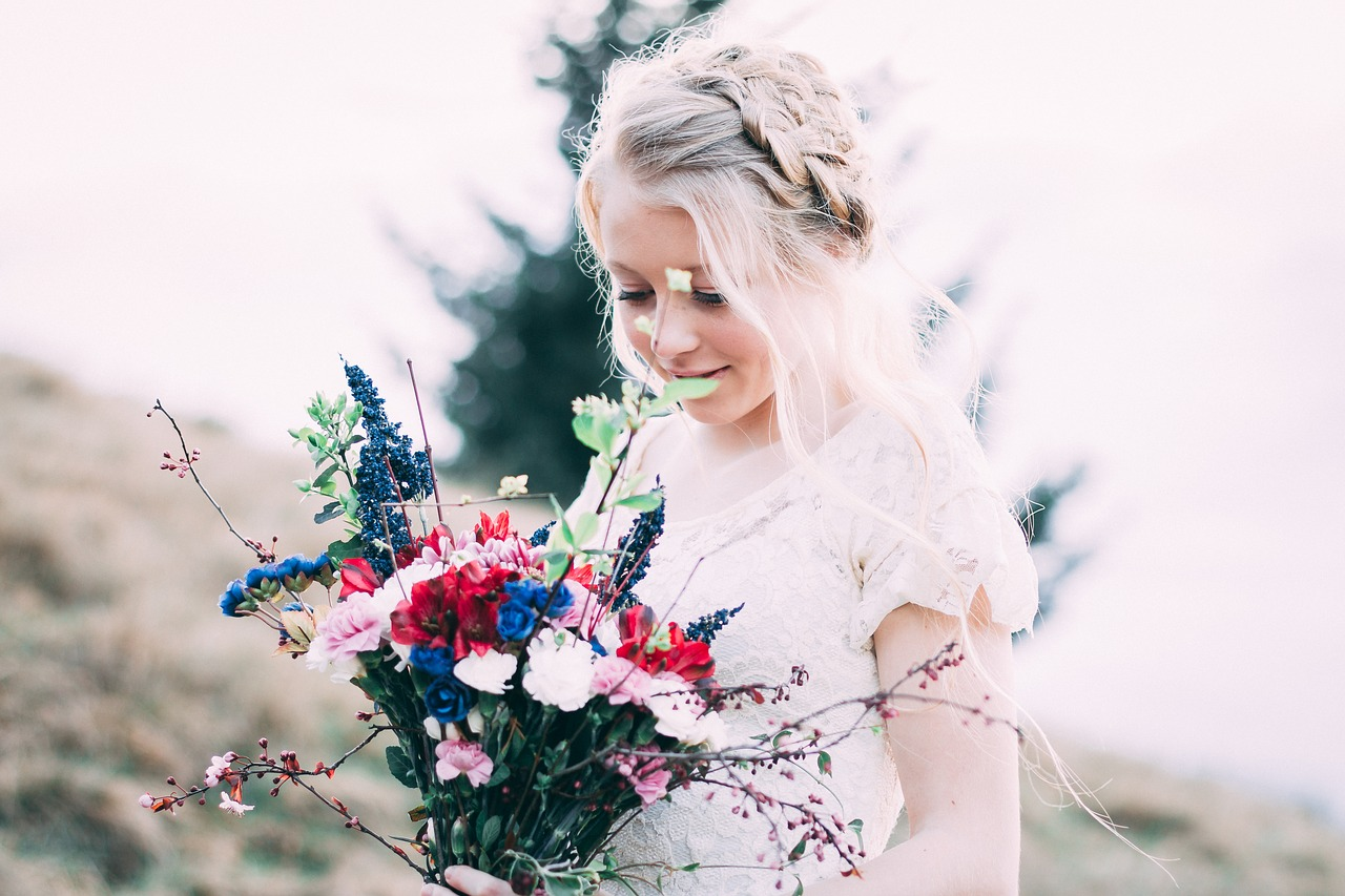 Bride in a field with wedding flowers.