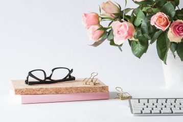 Part of a keyboard, glasses, and pink roses.