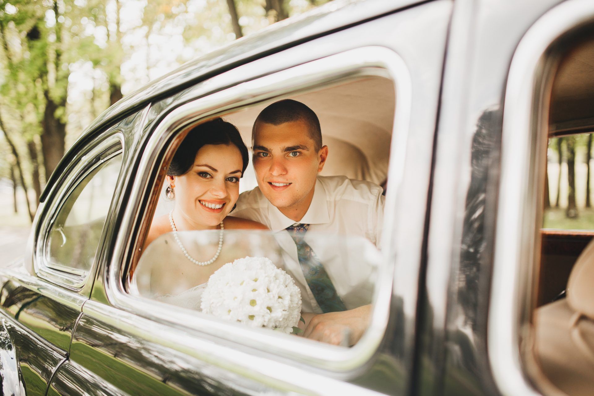 Bride and groom in the back seat of a car.