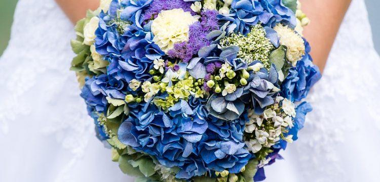 Bride holding blue bouquet.