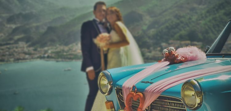 Bride and groom in front of a retro car.