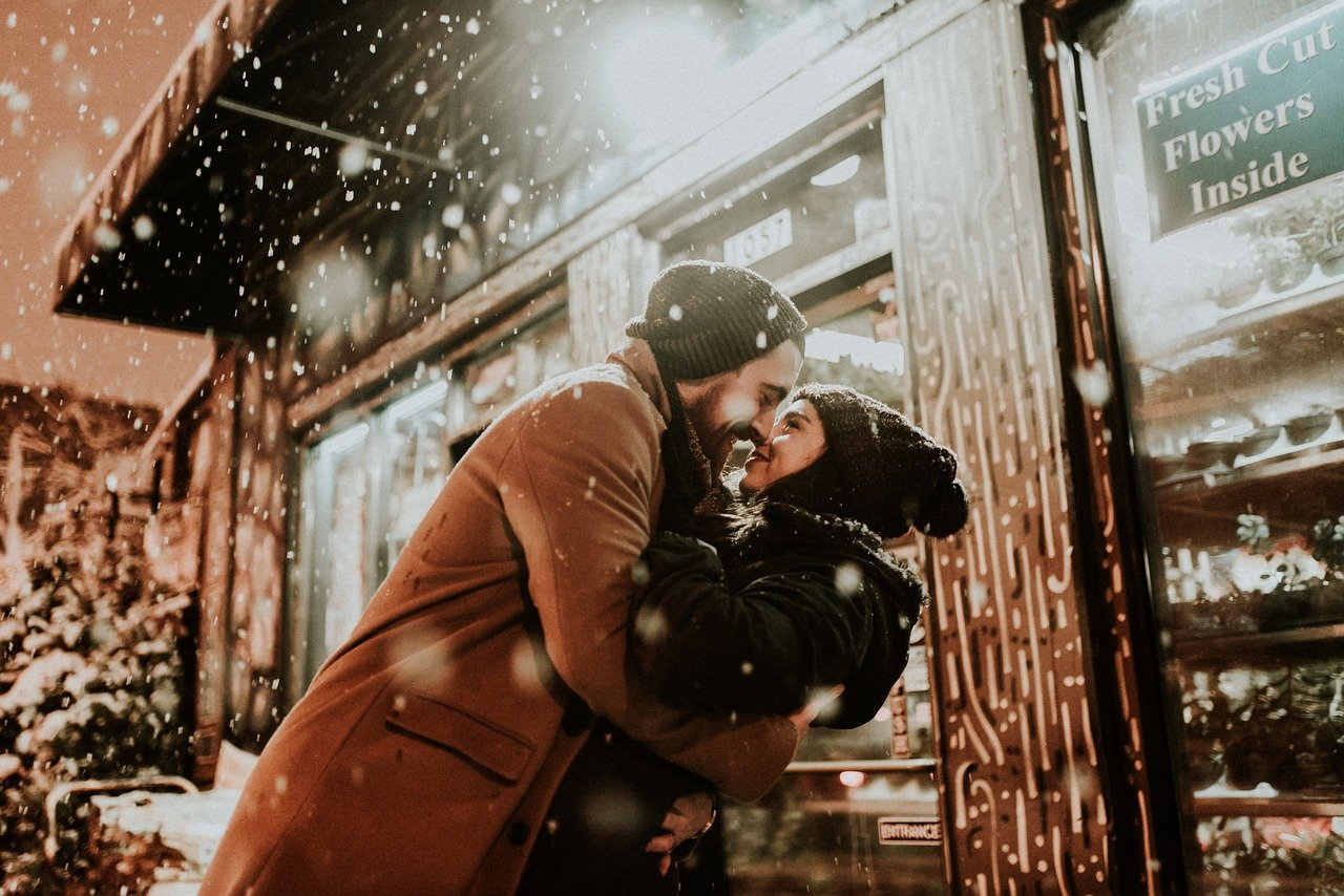 Man and woman embracing in the snow.