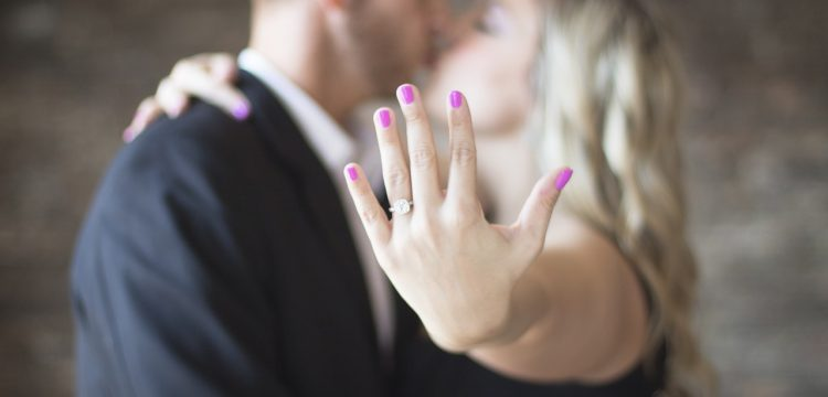 Man and woman kissing, with woman holding out hand with engagement ring on it.