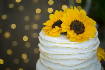 A single tiered wedding cake with a sunflower on top.