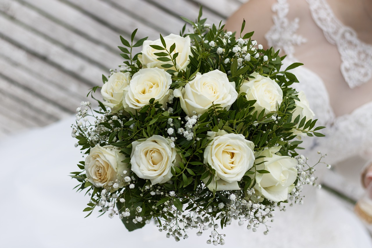 White roses with greenery in a wedding bouquet.