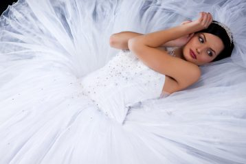 Bride laying down in a tulle covered wedding gown.