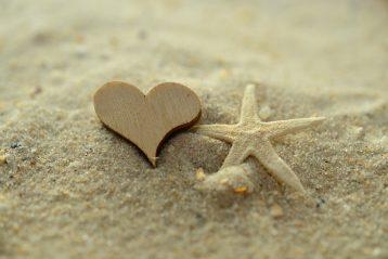 Heart drawn in sand on a beach.