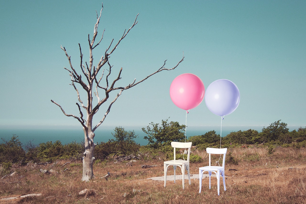 Balloons tied to white chairs.