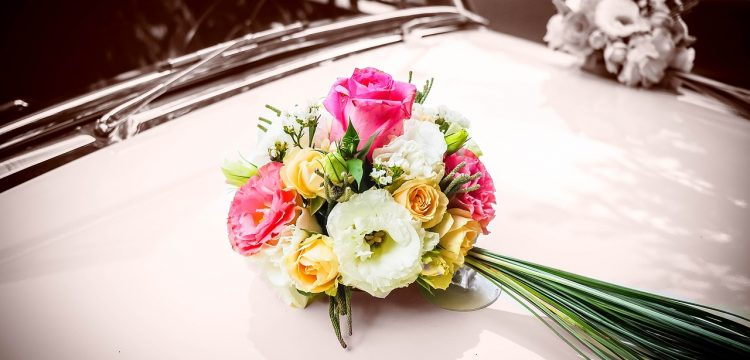 Bouquet of wedding flowers resting on a car hood.