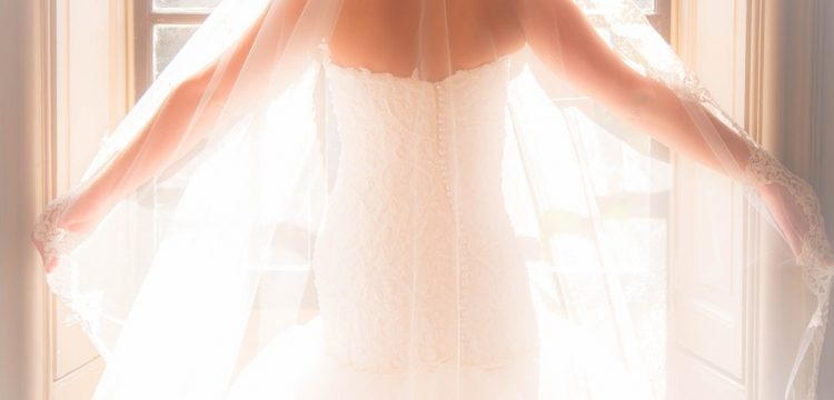 Bride standing in a window.