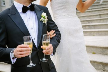 Groom holding two flutes of champagne.