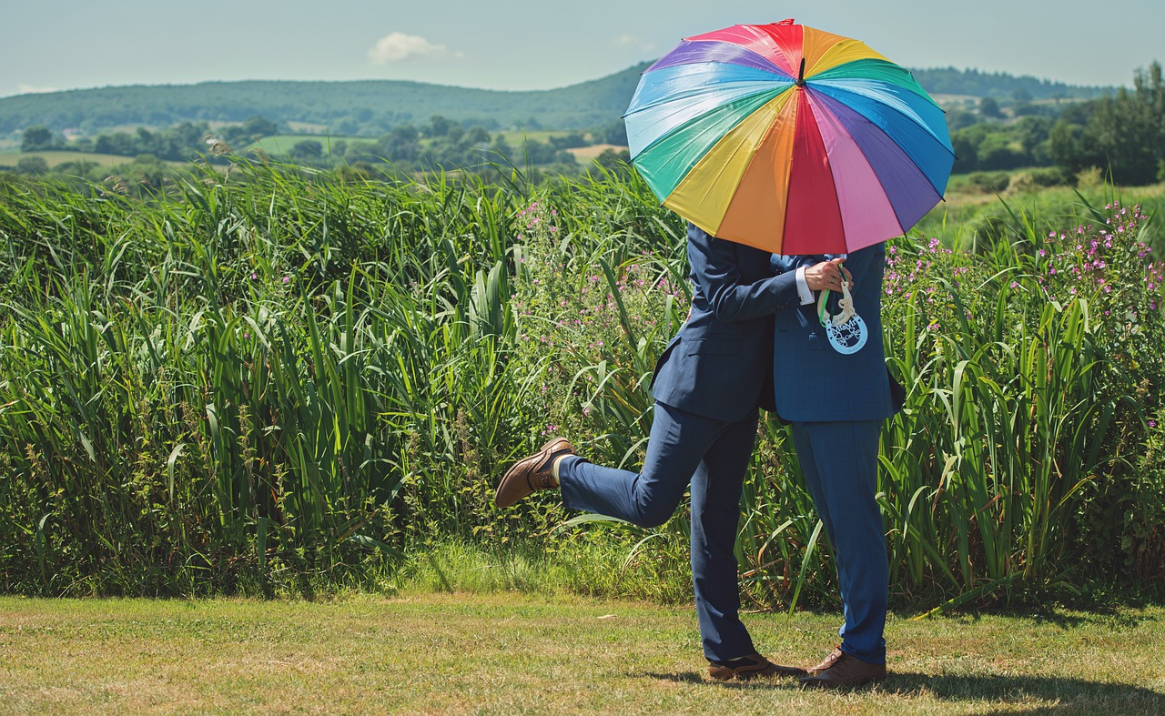 Two grooms with a rainbow umbrella.