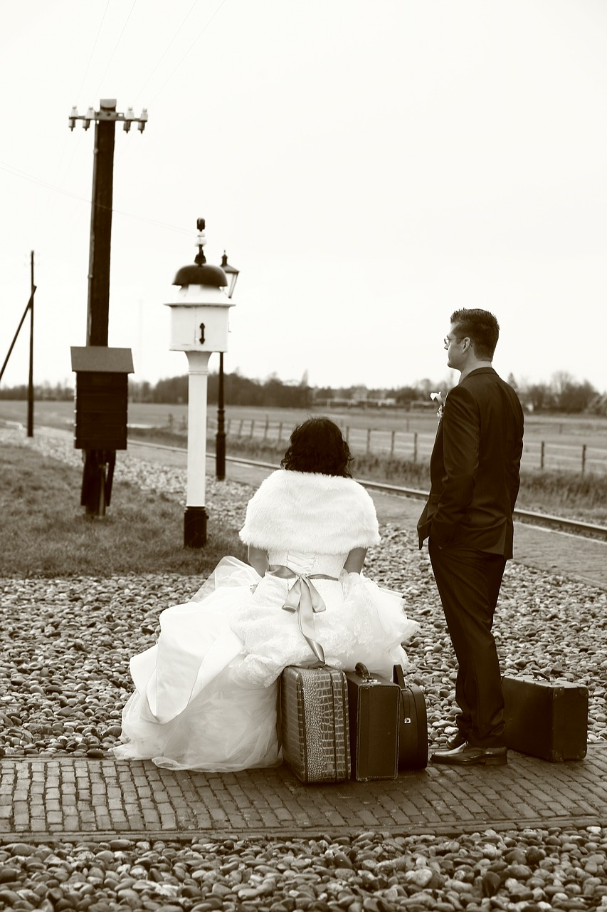 Couple waiting for a train with their luggage.