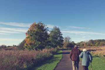 Older couple walking down a road.