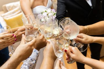 Bride, groom, and wedding guests toasting.
