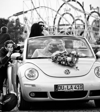 Photographer taking a picture of a bride and groom.