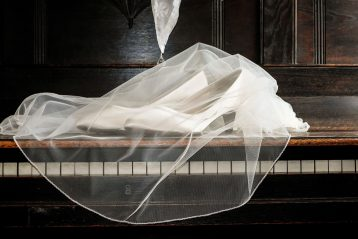 Wedding veil and shoes laying on a piano.