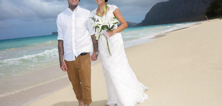 Bride and groom walking a Hawaiian beach.