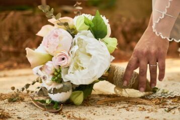 Bride's hand reaching for her bouquet.