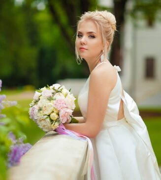 Bride with her bouquet, leaning on a railing.