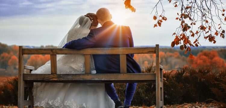 Bride and groom sitting on a bench in Fall.