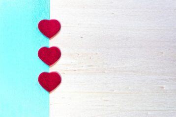 Wedding invitation with three red hearts.