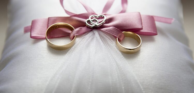 Wedding pillow with two rings tied to it.